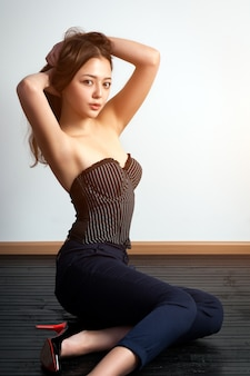 Asian young woman  in black top and classic black pants posing