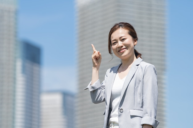 Asian young woman in a business outfit pointing up