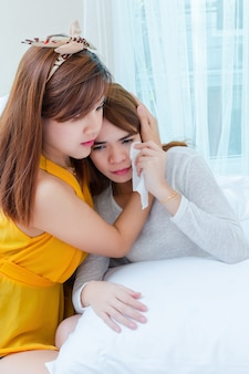 Asian young woman consoling crying female friend at home