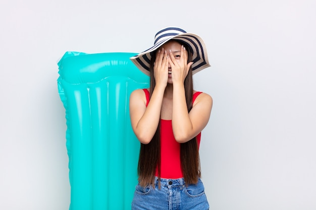 Asian young woman covering face with hands, peeking between fingers with surprised expression and looking to the side. summer concept