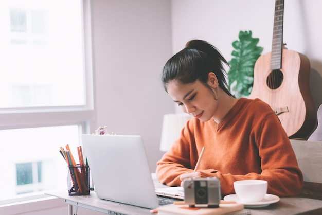 Asian young woman creative working on laptop computer in the morning - working from home concept