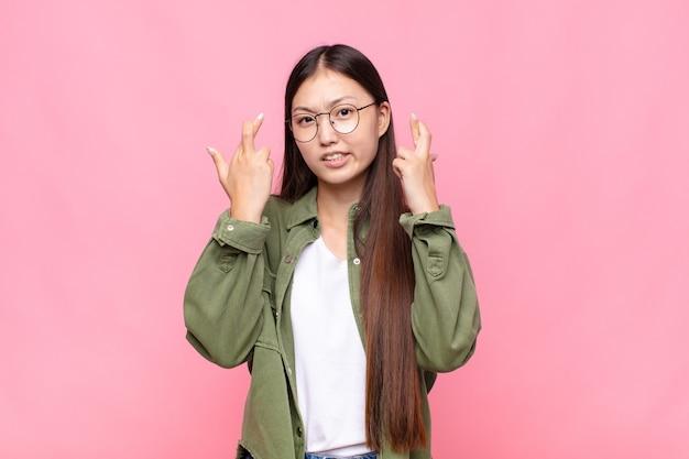 Азиатская молодая женщина с тревогой скрещивает пальцы и озабоченно смотрит на удачу