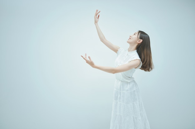 優雅に踊るアジアの若い女性と白い背景