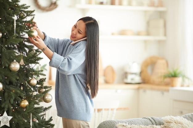 Asian young woman decorating christmas tree while talking on mobile phone in the living room