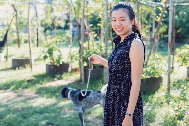 아침에 집에서 뒤뜰 정원에서 산책하는 아시아 젊은 여자 개