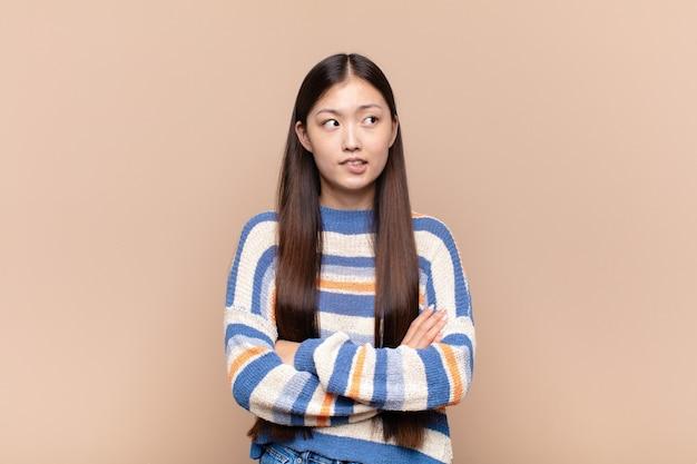 의심하거나 생각하고, 입술을 물고 불안하고 긴장된 느낌의 아시아 젊은 여성