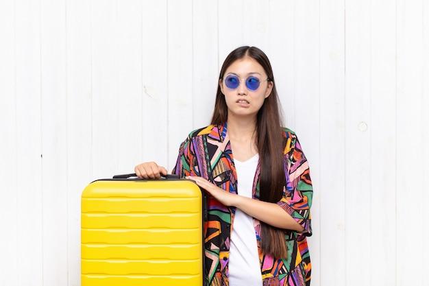 의심하거나 생각하고, 입술을 물고 불안감을 느끼는 아시아 젊은 여성