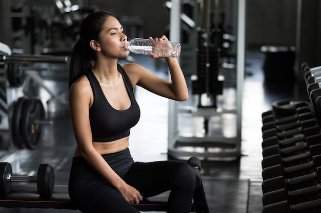 아시아 젊은 여성은 아령 운동이나 피트니스 체육관에서 운동을 하다가 휴식을 취한 후 물을 마신다