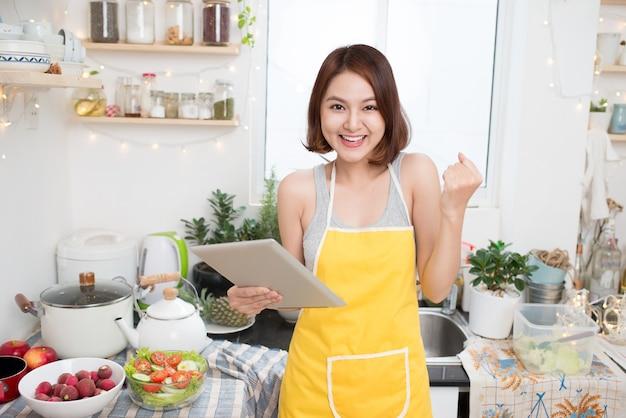 健康的な食事を食べ、タブレットコンピューターを使用してキッチンで料理をするアジアの若い女性