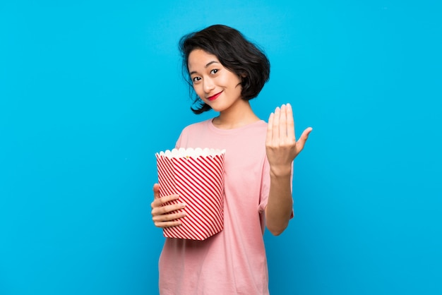 Asian young woman eating popcorns inviting to come with hand. happy that you came