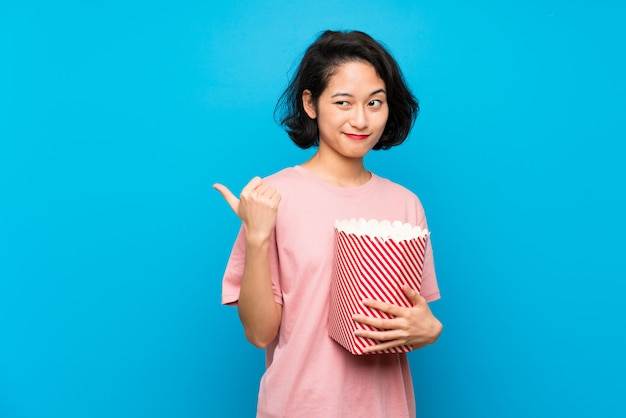 Asian young woman eating popcorns pointing to the side to present a product