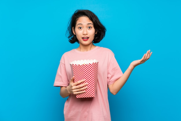 Asian young woman eating popcorns with shocked facial expression