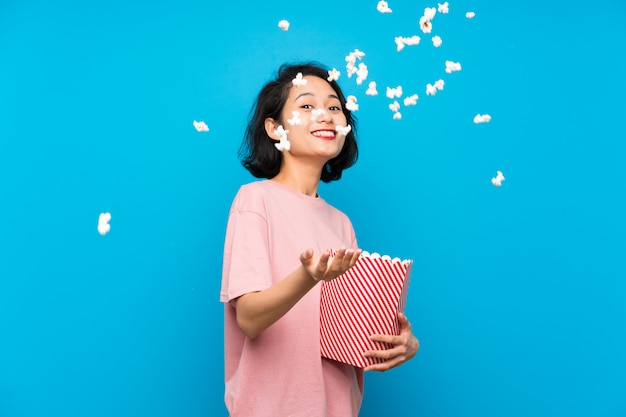 Asian young woman eating popcorns