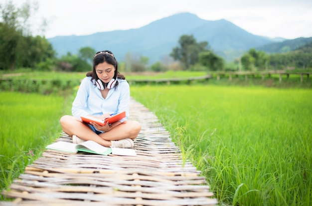 Asian young woman enjoy read books on wooden bridge in nature rice farm
