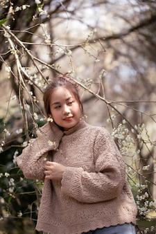 Азиатская молодая женщина наслаждаясь садом цветения сливы весной.