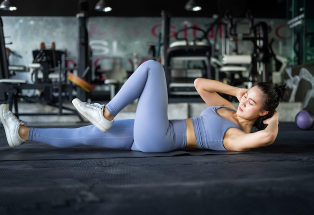 Asian young woman exercising in a gym doing leg raising and twisting exercises.