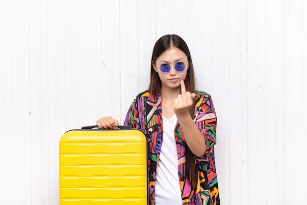 怒り、イライラ、反抗的、攻撃的なアジアの若い女性は、中指をひっくり返し、反撃します。休日の概念