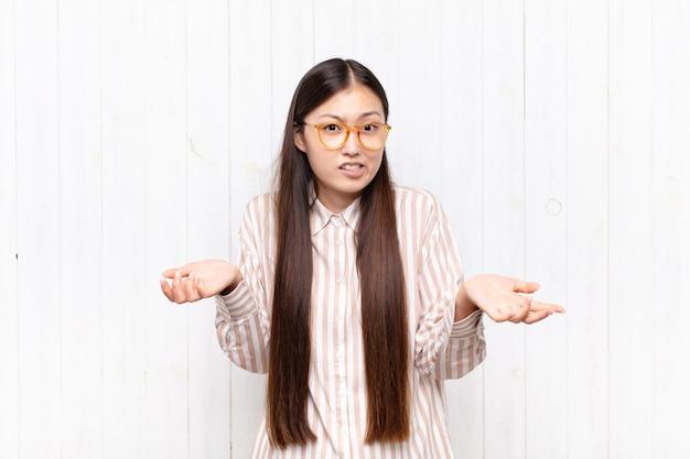 Азиатская молодая женщина чувствует себя невежественной и сбитой с толку, не уверенная, какой выбор или вариант выбрать, задается вопросом