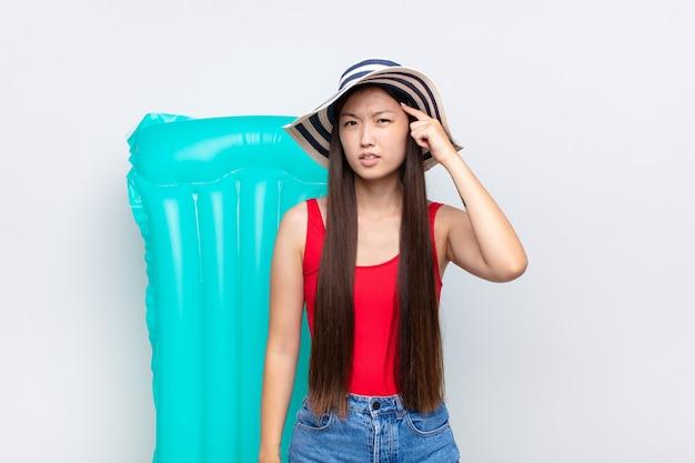 혼란스럽고 의아해하는 아시아 젊은 여성이 당신이 미쳤거나 미쳤거나 정신이 나갔음을 보여줍니다. 여름 개념