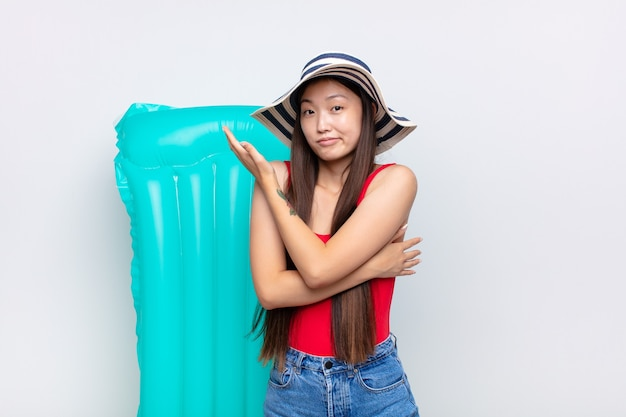 Asian young woman feeling confused and clueless, wondering about a doubtful explanation or thought. summer concept