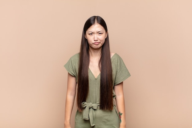 Asian young woman feeling confused and doubtful, wondering or trying to choose or make a decision