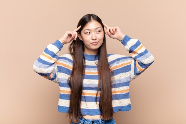 Asian young woman feeling confused or doubting, concentrating on an idea, thinking hard, looking to copy space on side