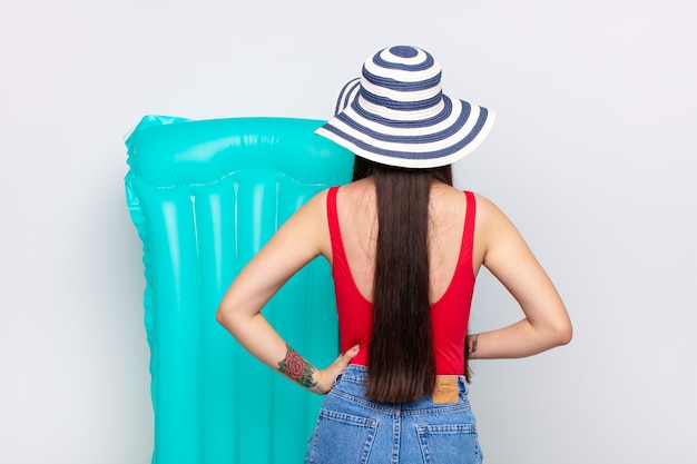 Asian young woman feeling confused or full or doubts and questions, wondering, with hands on hips, rear view. summer concept