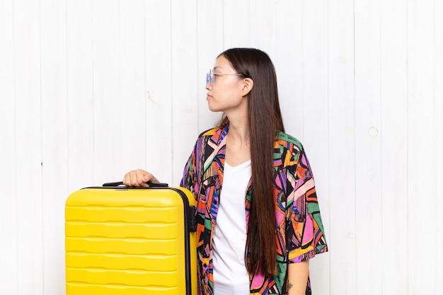 アジアの若い女性は、混乱したり、満腹になったり、疑問や質問を感じたり、疑問に思ったり、腰に手を当てたり、背面図を表示したりします。休日の概念