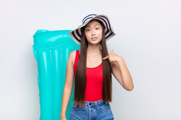 혼란스럽고 당혹스럽고 불안한 느낌이 드는 아시아 젊은 여성이 궁금해하고 누가 나에게 물어 보는지 가리키고 있습니다. 여름 개념