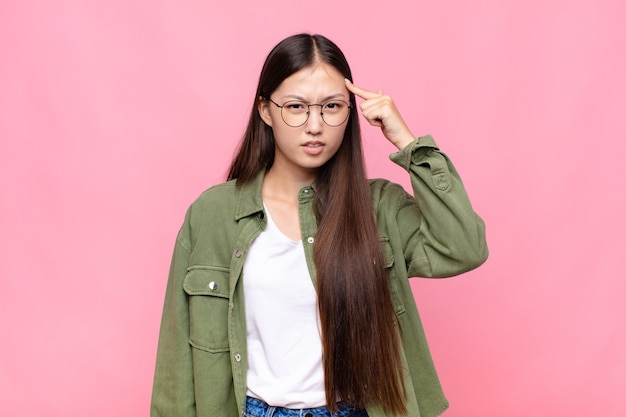 Asian young woman feeling confused and puzzled, showing you are insane, crazy or out of your mind