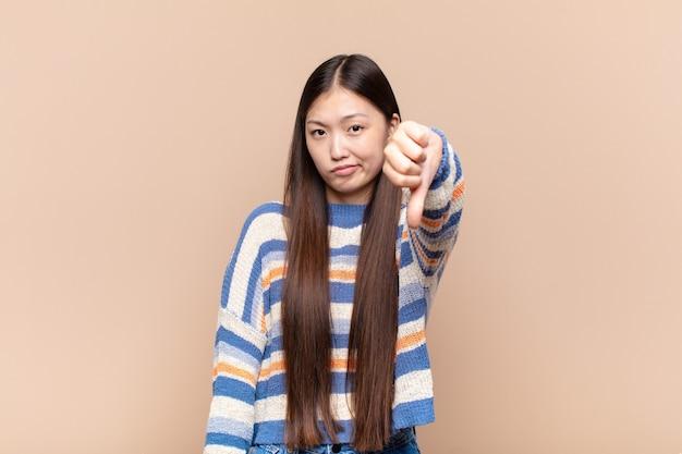 Азиатская молодая женщина чувствует себя раздраженной, сердитой, раздраженной изолированной