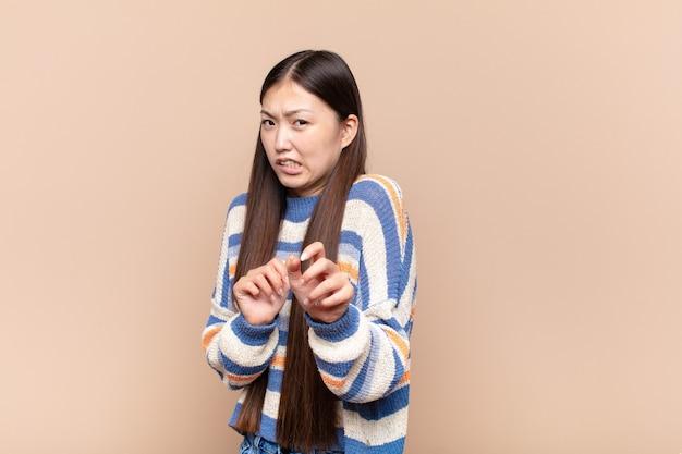 嫌悪感と吐き気を感じ、不快な、臭い、または臭いものから離れて、嫌なことを言っているアジアの若い女性