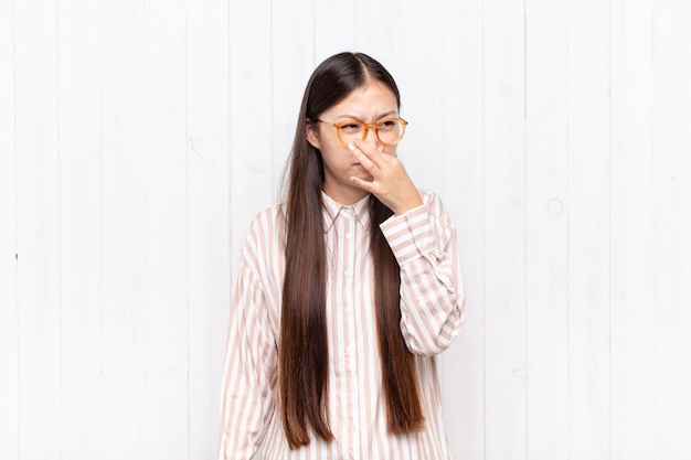 Asian young woman feeling disgusted, holding nose to avoid smelling a foul and unpleasant stench