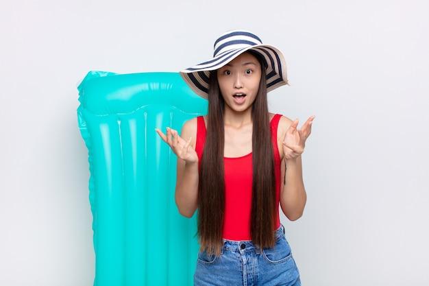 アジアの若い女性は、ストレスと恐怖の表情で、非常にショックを受け、驚き、不安とパニックを感じています。夏のコンセプト