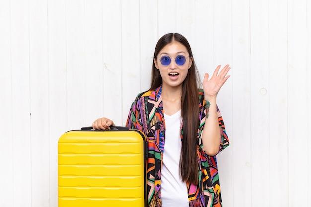Азиатская молодая женщина чувствует себя счастливой, пораженной, удачливой и удивленной, празднуя победу с поднятыми вверх обеими руками. концепция праздников