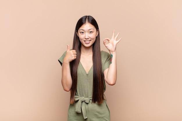 Азиатская молодая женщина чувствует себя счастливой, пораженной, удовлетворенной и удивленной, показывая хорошо и жесты подняв палец вверх, улыбаясь