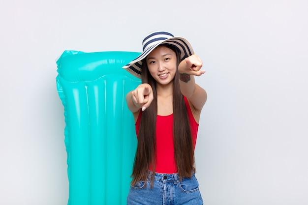 幸せで自信を持って、両手で正面を向いて笑い、あなたを選んでいるアジアの若い女性。夏のコンセプト