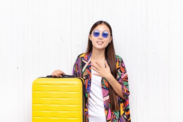 아시아 젊은 여성이 행복하고 사랑에 빠진 느낌, 심장 옆에 한 손으로 웃고 다른 한 손으로 앞쪽으로 뻗어 있습니다. 휴일 개념