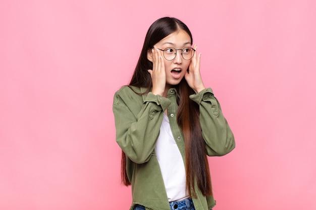 幸せ、興奮、驚きを感じ、顔を両手で横に見ているアジアの若い女性
