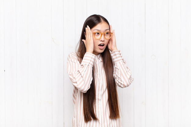 Азиатская молодая женщина чувствует себя счастливой, взволнованной и удивленной, глядя в сторону обеими руками на лице