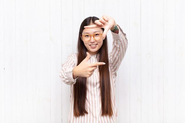 幸せ、フレンドリー、前向きな気持ち、笑顔、手でポートレートやフォトフレームを作るアジアの若い女性