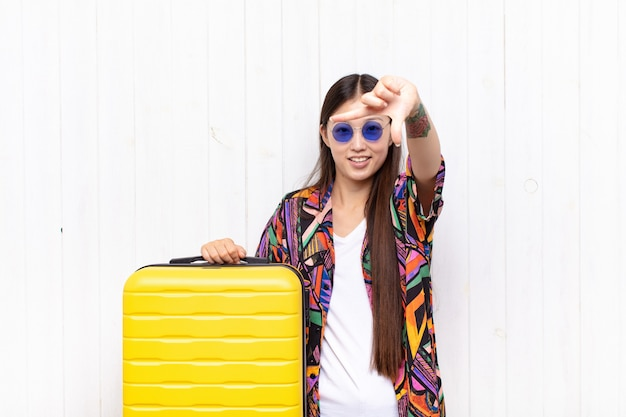 Asian young woman feeling happy, friendly and positive, smiling and making a portrait or photo frame with hands. holidays concept