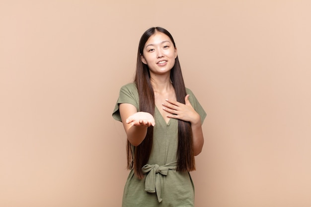 Asian young woman feeling happy and in love, smiling with one hand next to heart