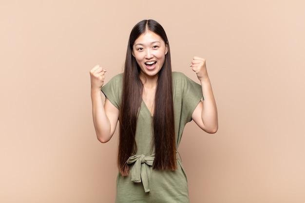 Азиатская молодая женщина чувствует себя счастливой, позитивной и успешной, празднует победу, достижения или удачу