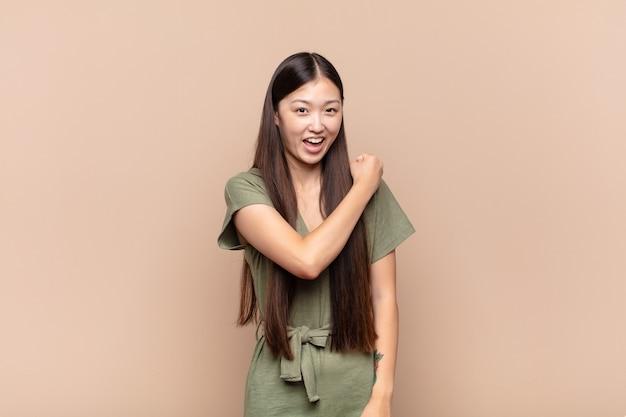 Азиатская молодая женщина чувствует себя счастливой, позитивной и успешной, мотивированной, когда сталкивается с проблемой или празднует хорошие результаты