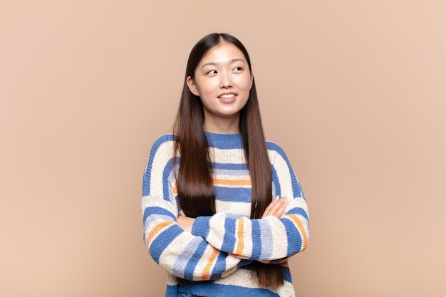 Asian young woman feeling happy, proud and hopeful, wondering or thinking, looking up to copy space with crossed arms