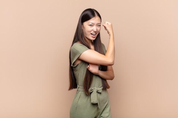 Азиатская молодая женщина чувствует себя счастливой, удовлетворенной и сильной