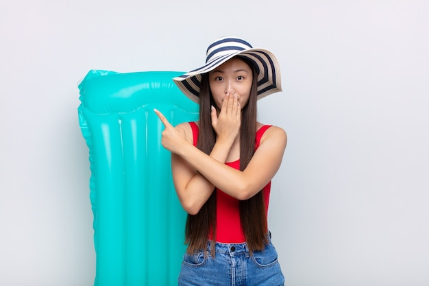 幸せ、ショック、驚きを感じ、手で口を覆い、横方向のコピースペースを指しているアジアの若い女性。夏のコンセプト