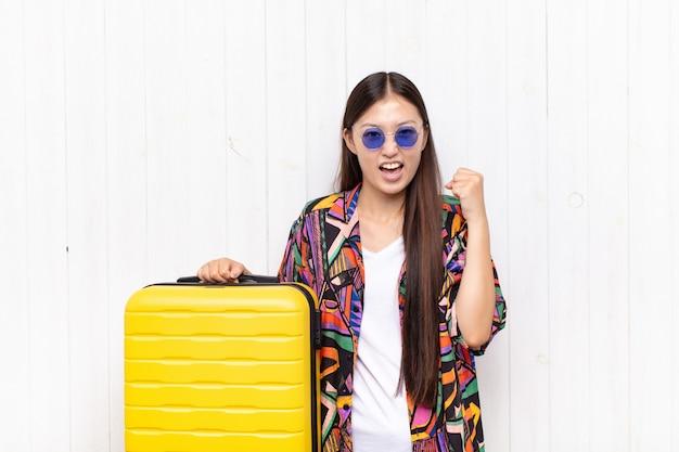 幸せ、驚き、誇りを感じ、大きな笑顔で成功を叫び、祝うアジアの若い女性。休日の概念