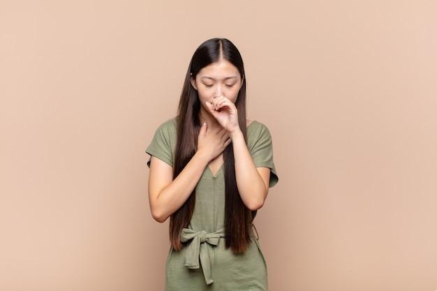 Азиатская молодая женщина чувствует себя плохо, с симптомами гриппа и болью в горле, кашляет с прикрытым ртом